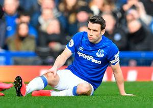 Everton's Irish defender Seamus Coleman holds his leg after receiving an injury during the English Premier League match against Manchester United at Goodison Park