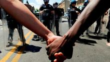 Members of the community hold hands in front of police officers in riot gear outside a recently looted and burned CVS store in Baltimore, Maryland. Photo: Reuters