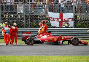 Ferrari Formula One driver Fernando Alonso (3rd L) of Spain looks at his car which stopped during the Italian F1 Grand Prix in Monza last weekend