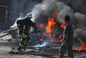 A civil defence member attempts to put out a fire from a burning vehicle at a site hit by what activists said was a barrel bomb dropped by forces loyal to Syria's President Bashar al-Assad in the Qadi Askar neighbourhood of Aleppo. Reuters/Abdalrhman Ismail