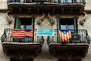 """A pro-Catalan independence flag (R) known as the """"Estelada"""" hangs from a balcony in central Barcelona as Catalonia participates in a symbolic independence vote. Hundreds of thousands of Catalans voted on Sunday in a symbolic vote on independence from Spain that supporters hope will propel the issue further despite opposition from Madrid. The """"consultation of citizens"""" in the wealthy northeastern region follows a legal block by the central government against a more formal, albeit still non-binding ballot which regional leaders had been pushing for. Photo credit: REUTERS/Paul Hanna"""