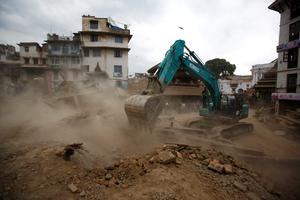 An excavator digs the rubble to search for the bodies after an earthquake hit, in Kathmandu, Nepal April 25, 2015. The powerful earthquake struck Nepal and sent tremors through northern India on Saturday, killing hundreds of people, toppling an historic 19th-century tower in the capital Kathmandu and touching off a deadly avalanche on Mount Everest. REUTERS/Navesh Chitrakar