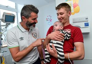 Republic of Ireland assistant manager Roy Keane with Karol Cearnowska, 9 months old, and her father Batiex, from Co. Fermoy, Co. Cork, during a visit to Temple Street Childrens Hospital, Dublin. Picture credit: David Maher / SPORTSFILE