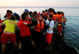 A Syrian refugee woman reacts as she and family members jump off a overcrowded dinghy after landing safely on the Greek island of Lesbos after crossing a part of the Aegean Sea from the Turkish coast (seen in the background), September 19, 2015. REUTERS/Yannis Behrakis