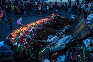 People lay flowers and pay their respects at a memorial for anti-government protesters killed in clashes with police in Independence Square on February 23, 2014 in Kiev, Ukraine.