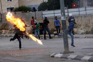 A Palestinian protestor throws a Molotov cocktail towards Israeli security forces during clashes to mark Nakba Day near the West Bank city of Ramallah