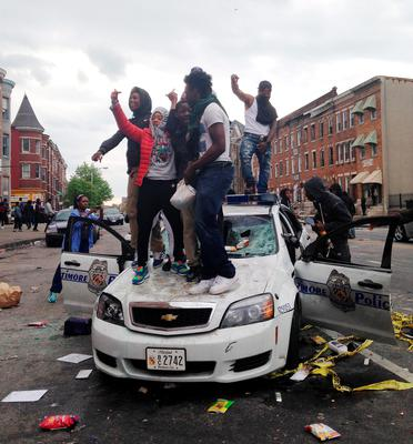 People stand on top of a Baltimore police car in Baltimore on Monday, April 27, 2015, during unrest following the funeral of Freddie Gray. Gray died from spinal injuries about a week after he was arrested and transported in a Baltimore Police Department van. (AP Photo/Juliet Linderman)