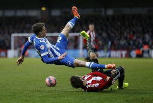 Solly March of Brighton & Hove Albion is tackled by Tommy Smith of Brentford