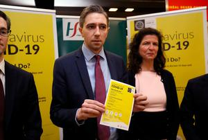 Health Minister Simon Harris holds a leaflet for the public awareness campaign for Covid-19 at Dublin Airport. Photo: Brian Lawless/PA Wire