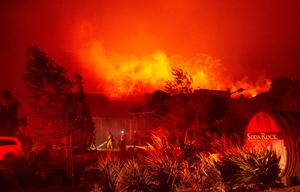 TOPSHOT - Firefighters survey Soda Rock Winery as it begins to burn during the Kincade fire in Healdsburg, California on October 27, 2019. Photo by Josh Edelson / AFP