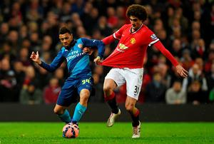 Arsenal midfielder Francis Coquelin holds off a challenge from Manchester United's Marouane Fellaini during the FA Cup quarter-final at Old Trafford. Photo: Laurence Griffiths/Getty Images