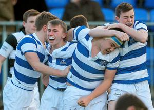 Adam Thompson, second from left with mouthguard, Blackrock College, and teammates, left to right, Liam Turner, Giuseppe Coyne and Niall Brady celebrare after Thompson scored the winning try in the final minute.