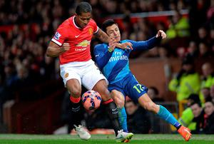Manchester United wing-back Antonio Valencia tussles with Arsenal's Alexis Sanchez during the FA Cup quarter-final at Old Trafford. Photo: OLI SCARFF/AFP/Getty Images