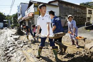 Schoolchildren and residents remove mud after flooding caused by Typhoon Hagibis in Marumori, Miyagi prefecture, Japan, October 13, 2019, in this photo taken by Kyodo. Mandatory credit Kyodo/via REUTERS