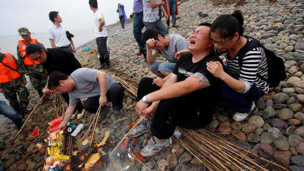 Family members of Eastern Star cruise ship victims burn offerings as they cry during a ceremony to mark seven days since the ship went down in the Jianli section of Yangtze River, Hubei province, China, June 7, 2015. REUTERS/Chen Zhuo/Yangzi River Daily