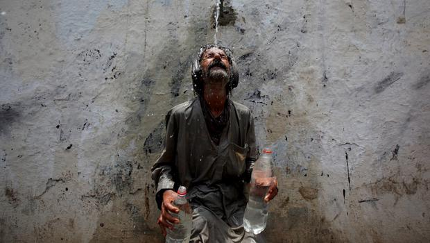 A man cools off from a public tap after filling bottles during intense hot weather in Karachi, Pakistan, June 23, 2015. A devastating heat wave has killed more than 400 people in Pakistan's southern city of Karachi over the past three days, health officials said on Tuesday, as paramilitaries set up emergency medical camps in the streets. REUTERS/Akhtar Soomro            TPX IMAGES OF THE DAY