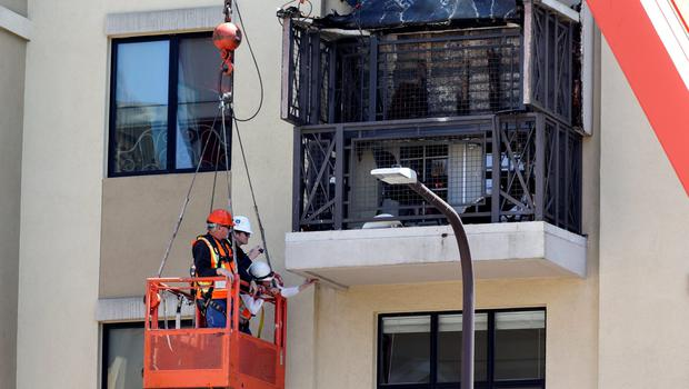 Workmen examine the damage at the scene of a 4th-story apartment building balcony collapse in Berkeley, California June 16, 2015. Six people were killed, including five young Irish citizens, and at least seven other people were injured when an apartment balcony collapsed early on Tuesday in the Californian city of Berkeley, Ireland's foreign minister said.  REUTERS/Elijah Nouvelage