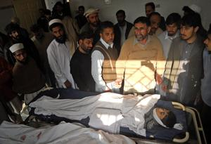 Pakistani relatives and mourners of a boy who was killed in a bomb blast gather around his body at a hospital in Kohat, Pakistan
