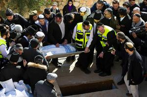The body of Francois-Michel Saada, one of four French Jews killed in an attack on a Paris kosher grocery, is lowered to the grave during their joint funeral in Jerusalem. Four French Jews killed in the attack on a kosher supermarket in Paris were buried in Jerusalem on Tuesday before thousands of French and Israeli mourners, with Prime Minister Benjamin)