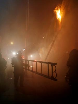 Baltimore fire fighters attack a fire set by rioters in a convenience store and residence on East Biddle street during rioting in Baltimore, Maryland in the early morning hours of April 28, 2015. REUTERS/Jim Bourg