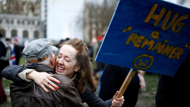 Anti-Brexit protester hugs a man while holding a placard on Brexit day in London, Britain January 31, 2020. REUTERS/Henry Nicholls