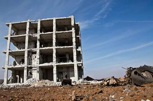 In this Wednesday, Nov. 19, 2014 photo, a destroyed building remains at the site of a truck bomb that exploded at a Kurdish People's Protection Units (YPG) stronghold. T(AP Photo/Jake Simkin)