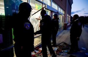"""Baltimore police officers arrive at a """"Deals"""" store just vandalised and looted by rioters as darkness falls during clashes between rioters and police in Baltimore, Maryland. Photo: Reuters"""
