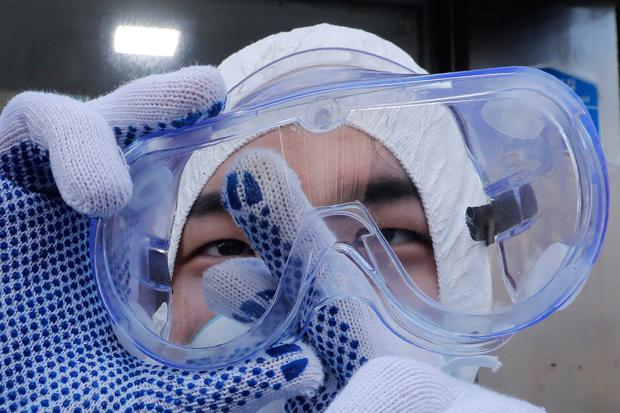 Preventative action: A worker cleans his goggles to spray disinfectant at a shopping street in Seoul, South Korea. Photo: AP