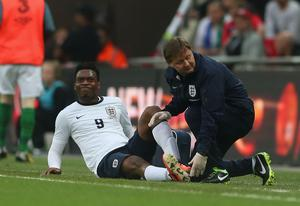 An injured Daniel Sturridge of England is given treatment by physio Gary Lewin. Photo credit: Scott Heavey/Getty Images