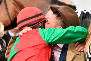 Jockey Sam Twiston-Davies is congratulated by breeder Frankie Dettori in the winner's enclosure after winning the Queen Mother Champion Chase on Dodging Bullets
