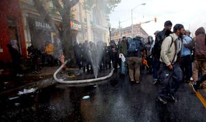 A fire hose cut by rioters sprays water into the air as protesters and a line of police move in at the site of a burning CVS drug store during clashes in Baltimore, Maryland. Photo: Reuters