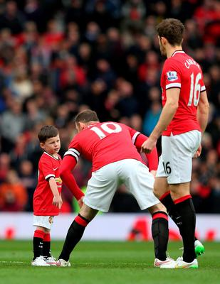 MANCHESTER, ENGLAND - MARCH 15:  Wayne Rooney of Manchester United runs out onto the pitch with his son Kai, who is a mascot for the day during the Barclays Premier League match between Manchester United and Tottenham Hotspur at Old Trafford on March 15, 2015 in Manchester, England.  (Photo by Alex Livesey/Getty Images)