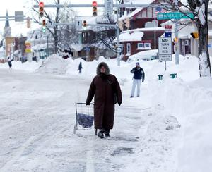 A woman walks along a snow-covered street in the south Buffalo area of New York. (AP Photo/Mike Groll)