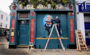WE CAN BE HEROES — JUST FOR ONE DAY: Artist Niall O'Loughlin painting a mural to Chief Medical Officer Tony Holohan at Devitts Pub on Camden Street, Dublin. Photo: Gareth Chaney/Collins