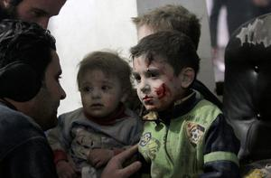 Children wounded after a bombing raid by President Assad's forces are treated by a doctor outside of Damascus