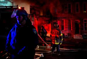 A police officer stands nearby as firefighters attack a fire in a convenience store and residence during clashes after the funeral of Freddie Gray in Baltimore, Maryland in the early morning hours of April 28, 2015. REUTERS/Eric Thayer
