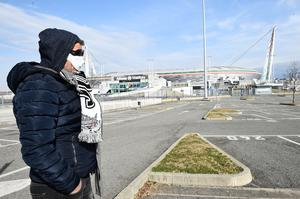 A man wearing a face mask is seen outside Juventus' Allianz Stadium in Turin , Italy after after five Serie A matches were postponed because of the ongoing coronavirus crisis. Photo: Reuters/Massimo Pinca