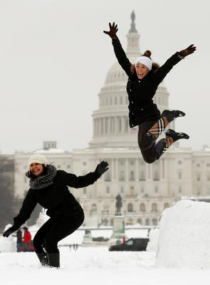 Adrienne Sipe (L) and Brooke Gilliam of Washington D.C. leap off a snow podium they made near the U.S. Capitol in Washington