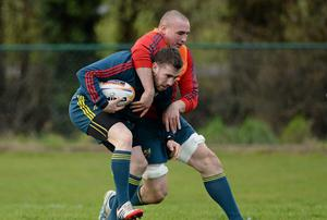 JJ Hanrahan is tackled by Tommy O'Donnell during the Munster training session at Bishopstown in Cork ahead of tomorrow's game against Scarlets