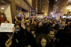 A crowd holds signs reading I am Charlie in French at a gathering in solidarity with those killed in an attack at the Paris offices of the weekly newspaper Charlie Hebdo on Wednesday, Jan. 7, 2015, outside of the French Consulate in San Francisco. (AP Photo/Marcio Jose Sanchez)