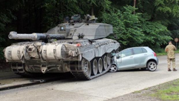 epa04779113 A handout photo provided by the Police department in Lippe on 01 June 2015 of a British 'Challenger 2' tank after it rolled over a car's front in Lippe, Germany, 01 June 2015. Police reported that a 18-year old female driving beginner from Detmold apparently overlooked a convoy of tanks when she turned left onto the Panzeringstrasse (lit. Tank Ring Road). The driver of the convoy'e leading tank, a 24-year old British national, was not able to stop his vehicle fast enough, hit the car and overran the vehicle's front. The young female car driver remained unhurt. The exclusive damage to the car was estimated at about 12,000 euro.  EPA/POLICE DEPARTMENT LIPPE / HANDOUTPolizei Lippe  HANDOUT EDITORIAL USE ONLY/NO SALES *** Local Caption *** 51970271