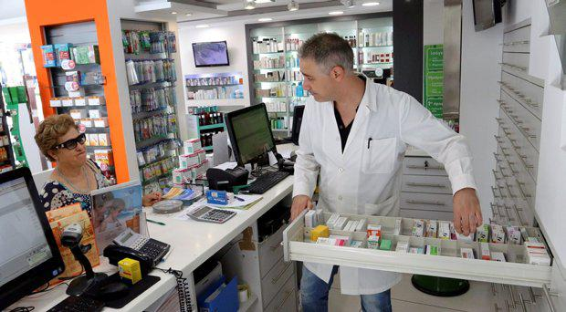 A pharmacist (R) searches for medicine for a client at a pharmacy at the city of Iraklio in the island of Crete, Greece July 7, 2015. Greece has enough medicine to last three to four months and drugmakers said on Monday that they would continue supplying the country for now, despite increased financial uncertainty after Greeks rejected austerity terms of a bailout