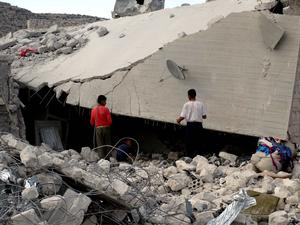 Residents inspect damaged buildings in what activists say was a U.S. strike, in Kfredrian, Idlib province.   Reuters