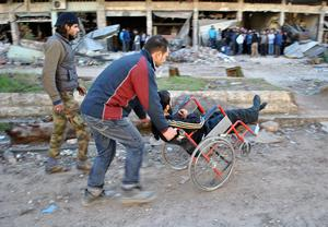 A Syrian man pushes an injured man in a wheelchair as they are evacuated during a humanitarian operation in the besieged Syrian city of Homs on February 10, 2014.