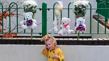 A Neighbour's child after placing flowers and teddy bears at the scene of an apartment fire in Clondalkin. Photo: Collins