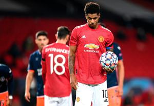Marcus Rashford of Manchester United takes the ball from team mate Bruno Fernandes to take a penalty, leading to scoring their team's third goal during the UEFA Champions League Group H stage match against İstanbul Basaksehir at Old Trafford. (Photo by Michael Regan/Getty Images)