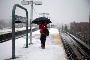 A man stands with an umbrella at the Junction Boulevard stop of the 7 subway train line in the Queens borough of New York January 26, 2015.  REUTERS/Shannon Stapleton