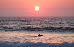 A surfer paddles out to catch a wave in Strandhill, Co. Sligo. Photo: Janell Carew