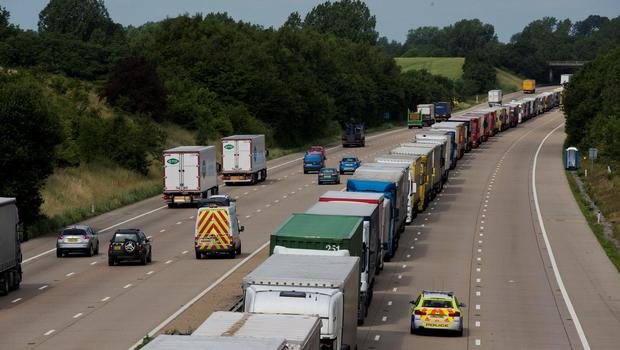A police vehicle passes by as lorries stand queued up between junctions 8 and 9 of the M20 motorway