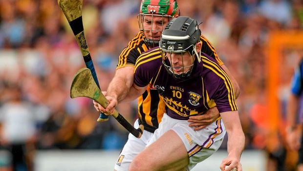 Shane Tomkins of Wexford is tackled by Kieran Joyce of Kilkenny